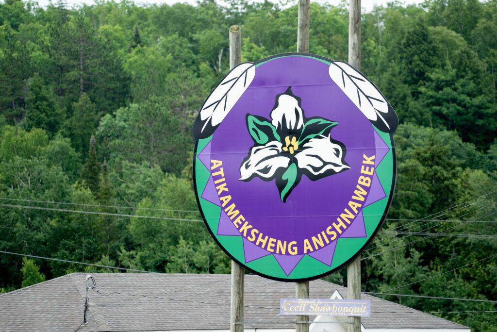 Billboard with Atikameksheng Anishnawbek logo